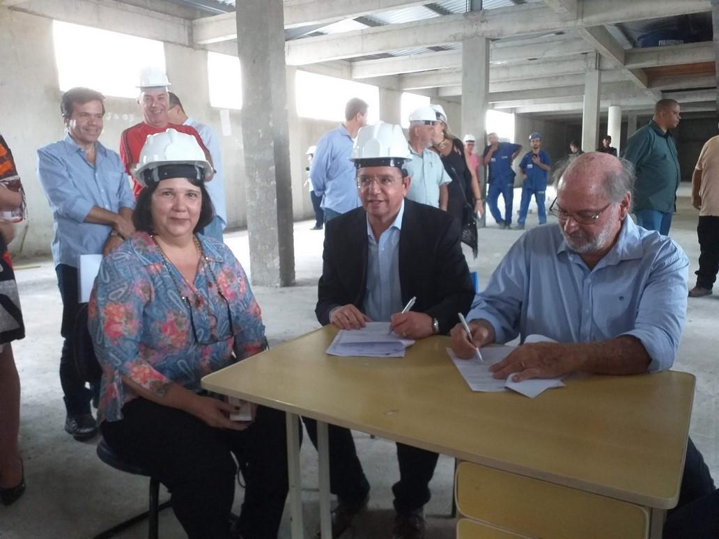Entre a secretária Tânia Trilha e Aurélio Mury, Bravo assina o contrato (Fotos: Paula Valviesse)