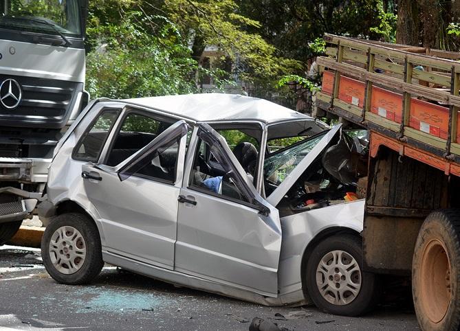 O carro espremido entre os dois caminhões (Fotos de Henrique Pinheiro e de leitores)