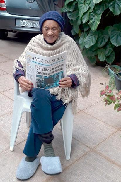 Dona Detinha lendo A VOZ DA SERRA: sem óculos