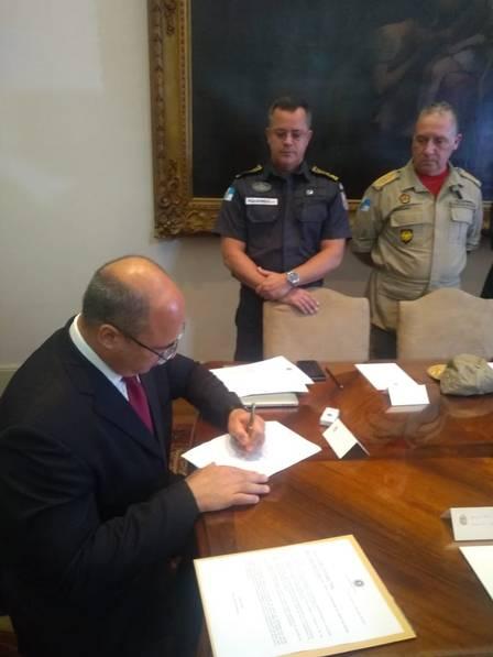 Wtzel assina o decreto diante de Figueredo e Robadey (Arquivo/ Divulgação)
